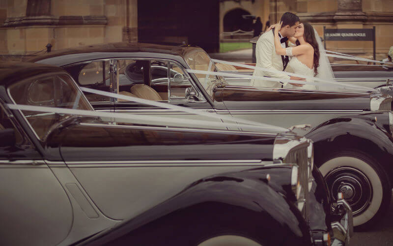 Classic black wedding cars with white walls.
